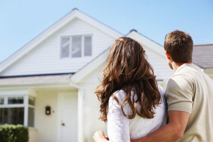 A young couple standing in front of the home they just purchased.