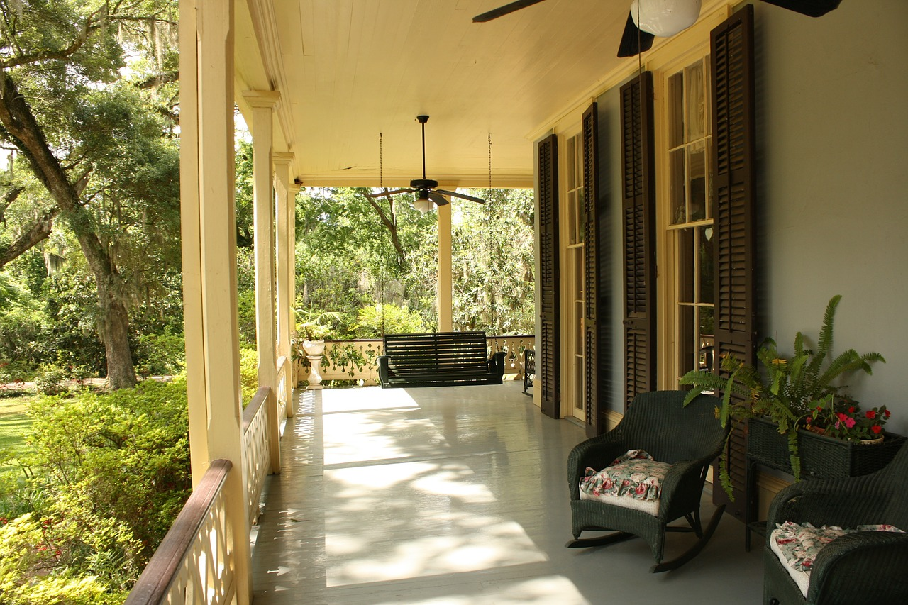 A spacious front porch with large shutters, deck furniture, and siding.