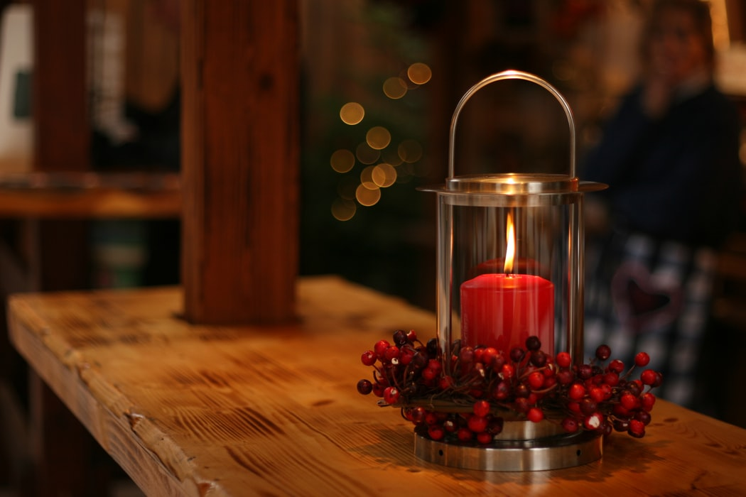 A cozy lit candle on a wooden bar.